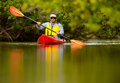 Man kayaking in florida young red kayak tropical destination Stock Photos