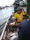 A man keeps enjoying food and drinks in his boat in a flooded street of Pathum Thani, Thailand, in October 2011. Royalty Free Stock Photo