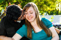 A man kisses his fiance on the cheek men she looks down with big smile and looks very content Stock Image