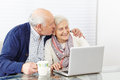 Man kissing senior woman at happy women the computer on the cheek Royalty Free Stock Images