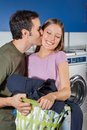 Man kissing woman on cheek at laundromat side view of young men women with basket of clothes Stock Photo