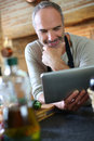 Man in kitchen checking recipe on internet mature reading tablet Stock Image