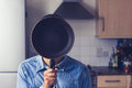 Man in kitchen holding a frying pan in front of his face young is hiding behind Royalty Free Stock Photos