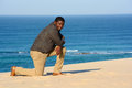 Man kneeling on beach an african american young in the sand the in front of blue sea background Stock Photos