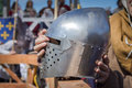 The man on the knight tournament holding a knight s helmet in ancient clothes Stock Photos