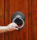Man knocks on the door s hand holds cast iron knocker old in italy Royalty Free Stock Photo