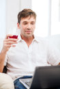 Man with laptop computer and glass of rose wine Royalty Free Stock Photo
