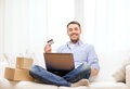 Man with laptop credit card and cardboard boxes technology home lifestyle concept smiling at home Royalty Free Stock Photo