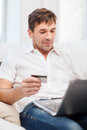 Man with laptop and credit card at home online or internet shopping concept smiling Stock Image