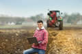 Man with laptop in the field young attractive peasant holding tractor ploughing background Royalty Free Stock Photo