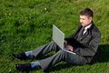 Man with a laptop on the grass Royalty Free Stock Images