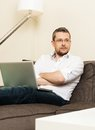 Man with laptop in home interior young fray hair on sofa Royalty Free Stock Photos