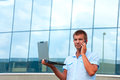 Man with laptop and mobile phone in front of modern business building Royalty Free Stock Image
