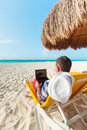 Man with laptop relaxing on the deckchair Royalty Free Stock Images
