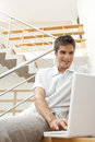 Man with Laptop on Stairs Smiling Stock Images