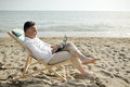 Man with laptop working on the beach sitting on a deckchair Royalty Free Stock Photo