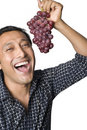 Man laughing and eating grapes Royalty Free Stock Photos