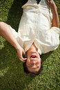 Man laughing while using a phone as he lies on the grass Royalty Free Stock Photo
