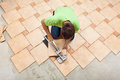 Man laying ceramic floor tiles working with a cutter device top view Stock Photo