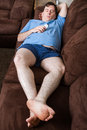 Man laying down on the couch wide angle view of holding remote Royalty Free Stock Images