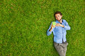Man laying on a grass talking on a mobile phone Royalty Free Stock Photo