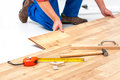 Man laying laminate flooring carpenter worker installing in the room Royalty Free Stock Photography