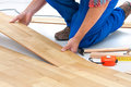 Man laying laminate flooring carpenter worker installing in the room Stock Photography