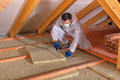 Man laying thermal insulation layer cutting the panels under roof using mineral wool Stock Images