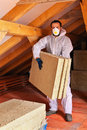 Man laying thermal insulation layer under the roof carry mineral wool panels Royalty Free Stock Photos
