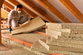 Man laying thermal insulation layer under the roof installing using mineral wool panels Stock Photo
