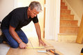 Man laying wood panel flooring during a house refurbishment Royalty Free Stock Photos