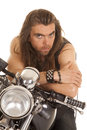 Man lean forward on motorcycle a leaning his handle bars with a serious expression his face Stock Photos