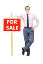 Man leaning on a for sale sign isolated white background Royalty Free Stock Images