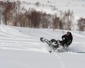 Man Leaning the snowmobile right over in the backcountry Royalty Free Stock Photo