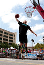 Man leaps to jam basketball in outdoor slam dunk contest athens ga usa august a young jumps above the rim a the competition of a Royalty Free Stock Images