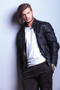 Man in leather jacket leaning against a gray wall relaxed young with hands pockets Stock Photo