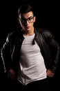 Man in leather jacket wearing glasses with hands on waist Royalty Free Stock Photo