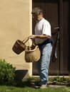 Man leaving home with baskets Stock Photos