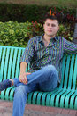 Man with leg crossed sitting on a bench Royalty Free Stock Images