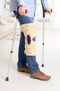 Man with leg in knee cages and crutches for stabilization and support Stock Images