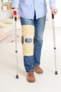 Man with leg in knee cages and crutches for stabilization and support Stock Photo