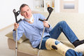 Man with leg in knee cages neck brace and crutches for stabilization and getting up for rehabilitation Royalty Free Stock Photos