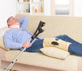 Man with leg in knee cages neck brace and crutches for stabilization and support resting on a sofa Stock Photo