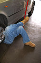 Man with legs crossed working under a car his as he works Royalty Free Stock Photo