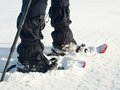 Man legs with snowshoes walk in snow. Detail of winter hike in snowdrift Royalty Free Stock Photo