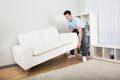 Man lifting couch young handsome in living room Royalty Free Stock Photos