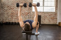 Man lifting dumbbells while lying on exercise bench Royalty Free Stock Photo
