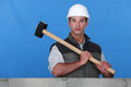 Man lifting hammer next to wall Stock Photos
