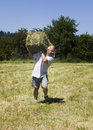 Man lifting hay bale Stock Photo