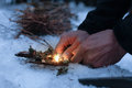 Man lighting a fire in a dark winter forest Royalty Free Stock Photo